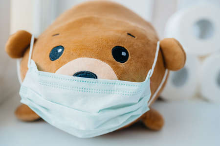 Disposable medical protective face mask on brown teddy bear Banque d'images