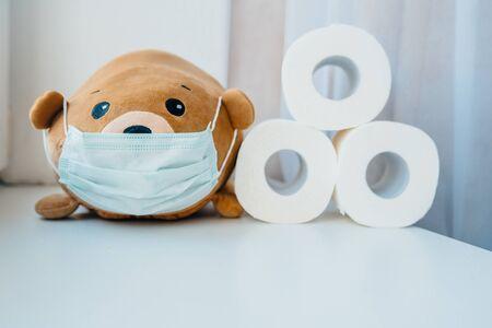 Disposable medical protective face mask on brown teddy bear Stok Fotoğraf