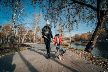 Happy mother and her daughter walk with dog in autumn park Banque d'images