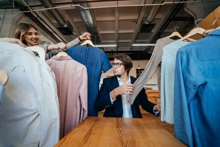 Young stylist looking through set of shirts for fashion shooting