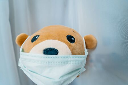 Disposable medical protective face mask on brown teddy bear Imagens