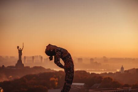 Woman doing yoga on the roof of a skyscraper in big city.