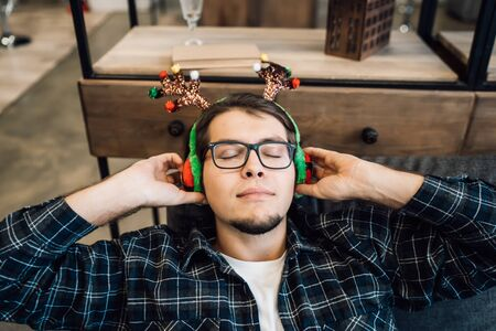 Happy man in headphones relaxing on the sofa at home