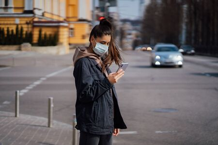Girl in protective mask using smartphone outdoors. COVID 19. World coronavirus pandemic.