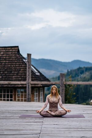 A woman sitting in lotus position at the morning on a fresh air. Banque d'images