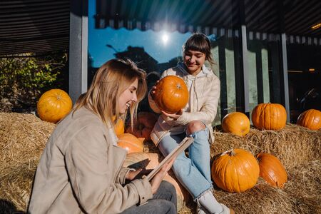 Girls have fun among pumpkins and haystacks on a city street