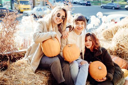 Girls holds pumpkins in hands on the background of the street. Banque d'images