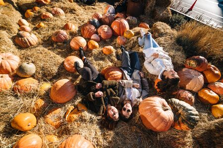 Young girls lie on haystacks among pumpkins. View from above Banque d'images