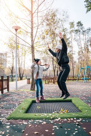 Mom and her daughter jumping together on trampoline in autumn park