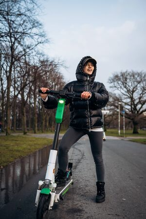 Woman in a jacket on an electric scooter in an autumn park.