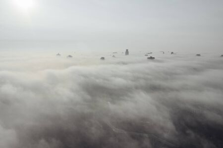 Aerial view of the city in the fog. Skyscrapers above the fog 免版税图像