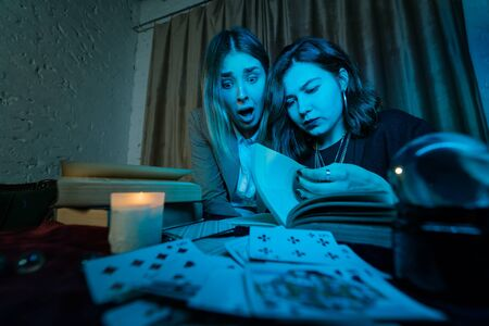 Two women are reading a mysterious book