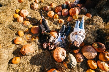 Young girls lie on haystacks among pumpkins. The concept of rural areas in a modern city. Photo Zone