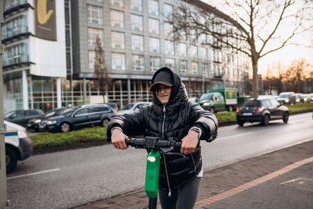 Woman in a jacket on an electric scooter in an autumn city.