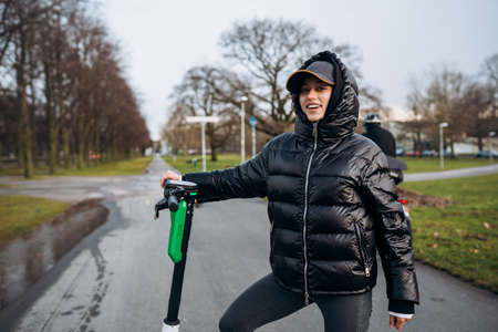 Woman in a jacket on an electric scooter in an autumn park. Stockfoto