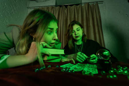 Fortune teller forecasting the future to woman with cards Stock Photo