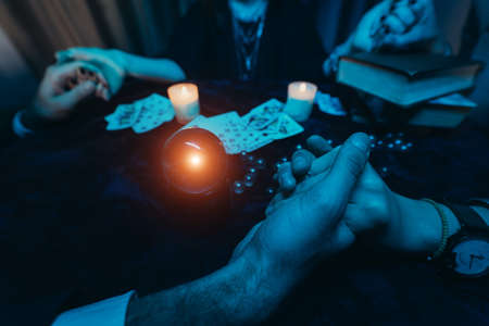 People hold hands of night at table with candles