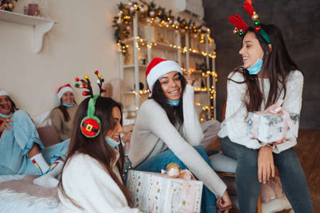 Multiethnic group of friends in Santa hats with gifts in hands. Stok Fotoğraf