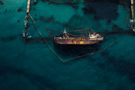 Top view of an old tanker that ran aground and overturned