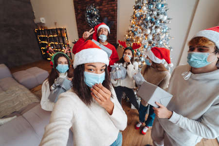 Multiethnic group of friends in Santa hats with gifts in hands. 版權商用圖片