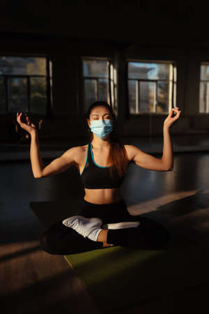 Sporty woman practicing yoga wearing protective mask