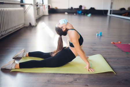 Sporty woman practicing yoga wearing protective mask Banco de Imagens