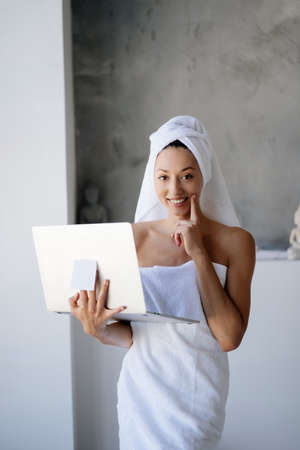 Woman freelancer in white towel stand in the bathroom with a laptop Stock fotó