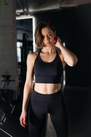 Portrait of Confident Brunette Woman Wearing Performance Wear in Gym