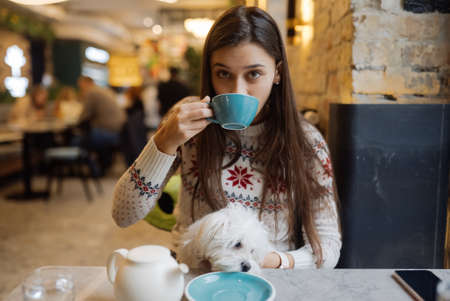 Beautiful woman is holding her cute dog, drinking coffee in cafe Banque d'images