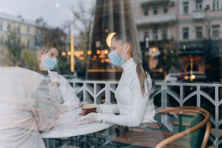 Friends girls met in a cafe. Wear medical protective masks. Banque d'images