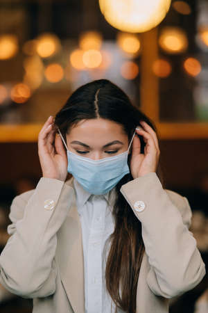 Girl in takes off her protective medical face mask