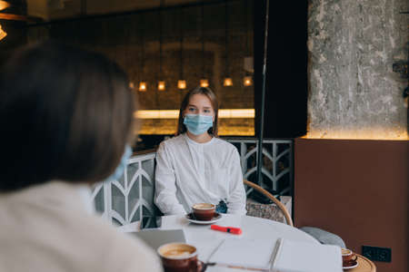 Two pretty women wearing medical face mask at cafe. Banque d'images