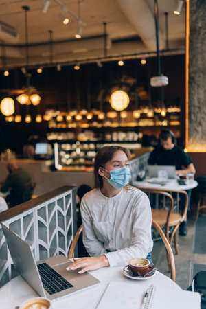 Pretty woman wearing medical face mask, using laptop to work.