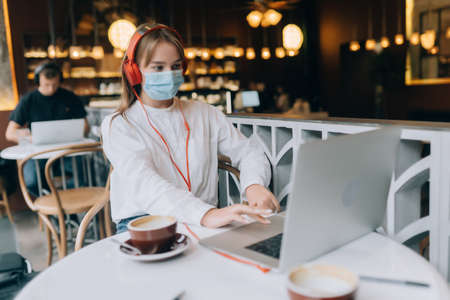 A girl sitting in a coffee shop with headphones.