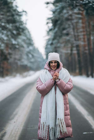 Portrait of a beautiful caucasian woman on a road through snowy forest