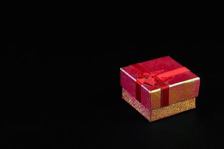Gristmass gift in red paper isolated at black background