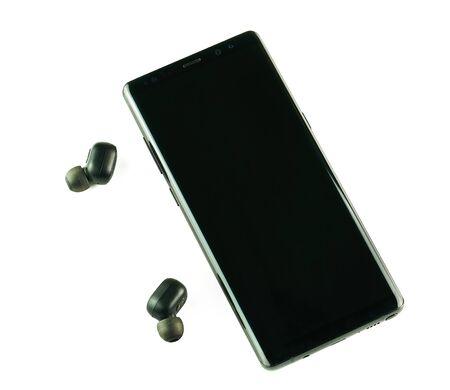 Smartphone with wireless headphones isolated