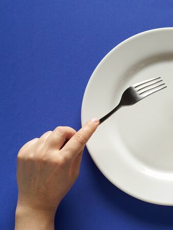 Fork and knife in hands on cobalt color background with white plate.