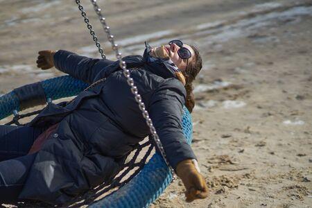 12-10-2018 Riga, Latvia woman on a swing on a seashore