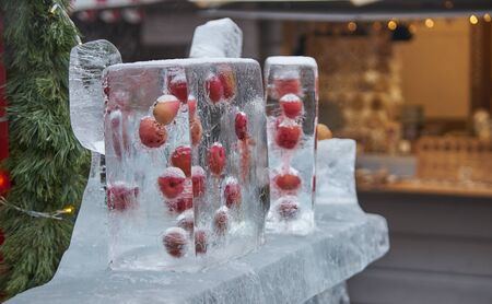 Red apples frozen in ice cube