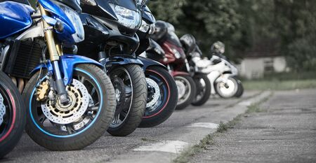 motorcycles standing in the row on asphalt closeup. Selective focus.