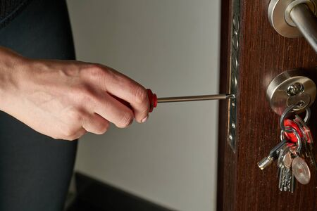 Closeup of a professional locksmith installing or repairing a new deadbolt lock on a house exterior door with the inside internal parts of the lock visible..