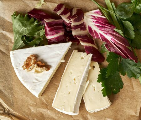 White delicious homemade camambert cheese on a wooden plate served with almonds, cashew, pine nuts and peach. Dessert for a family dinner. Brie Stock Photo