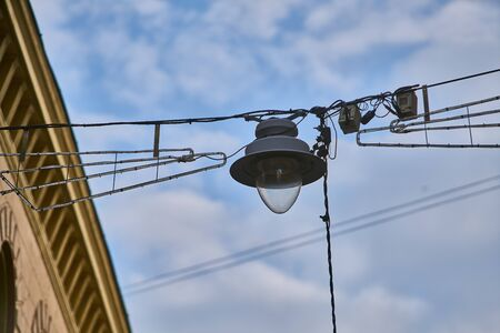 Urban view. Street lamps on aerial wires against cloudy blue sky.
