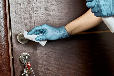 Disinfect door handle with sanitizer to prevent infection of coronavirus.