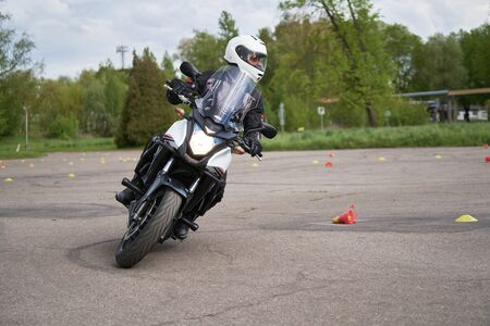 Motorcyclists ride through cones. Exersice for beginners and experienced. Free skill training as gymkhana for all people.