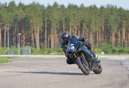 12-06-2020 Riga, Latvia. Fast motorbike racing on the race track at high speed. Composite image with heavy image editing