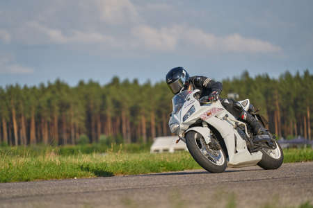 12-06-2020 Riga, Latvia. Motorcycle rider in a white helmet and gear racing at high speed on race track with motion blur. Sports theme racing.