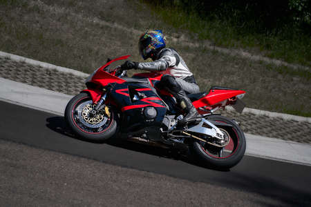 Man riding motorcycle in asphalt road curve with rural,motorcycle practice leaning into a fast corner on track 写真素材 - 150717159