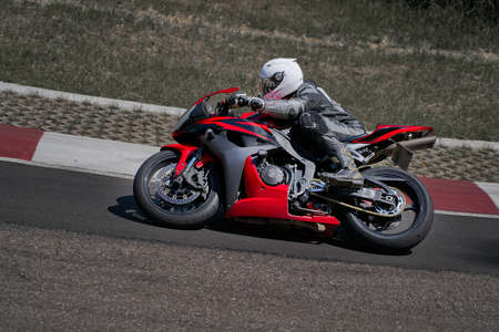 Man riding motorcycle in asphalt road curve with rural,motorcycle practice leaning into a fast corner on track 写真素材 - 150717170